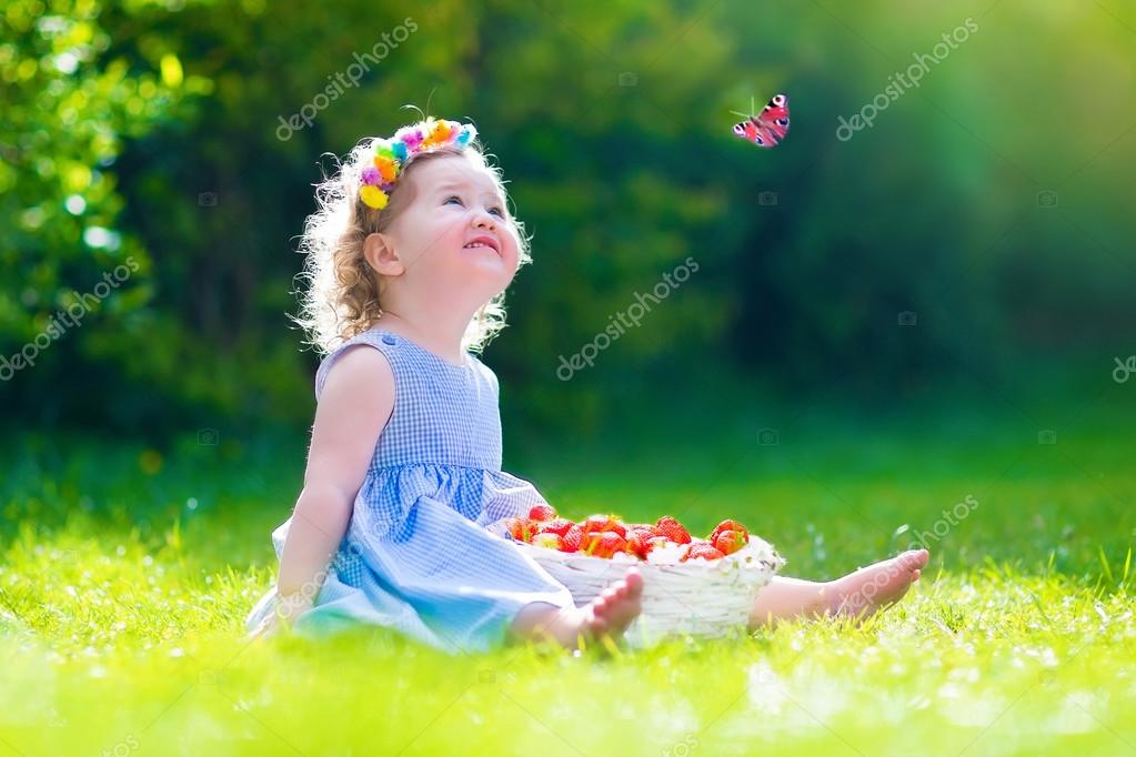 Little girl eating strawberry watching a butterfly