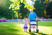Photo Senior lady with a walker and little girl in a park