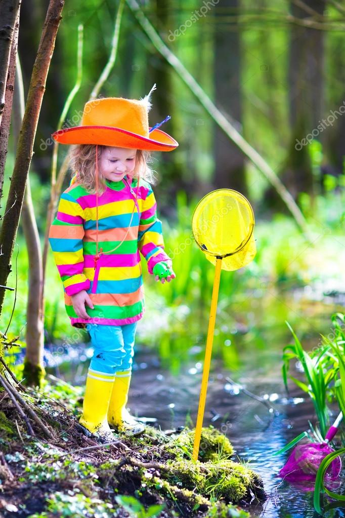 Little girl playing outdoors catching a frog
