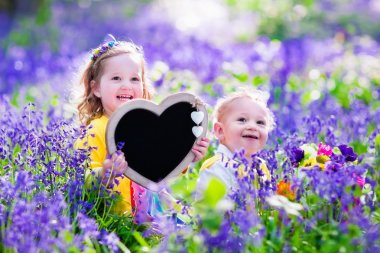 Children playing in bluebells forest. Little girl and baby boy holding a wooden heart shape chalk board standing in a park with beautiful spring bluebell flowers. Copy space for your text. Kids having fun outdoors in spring. stock vector