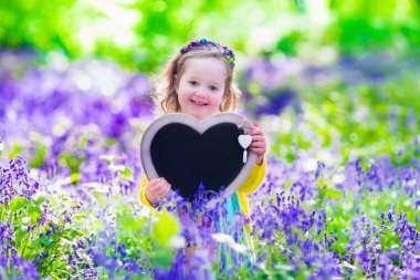 Описание: Child playing in bluebells forest. Little girl holding a wooden heart shape chalk board standing in a park with beautiful spring bluebell flowers. Copy space for your text. Kids having fun outdoors in spring. stock vector
