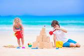 Fotografie Kinder bauen Sandburg am Strand