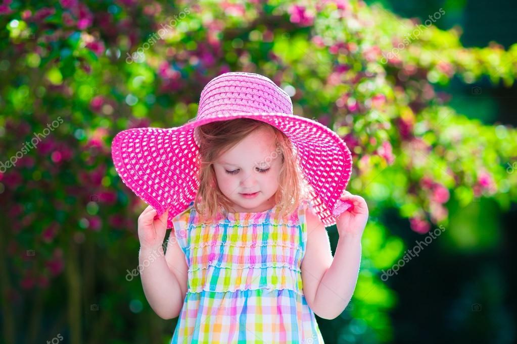 Little girl in a hat in blooming summer garden