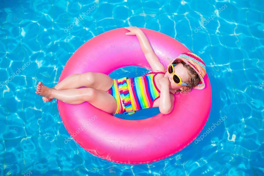 Cute little girl playing in swimming pool