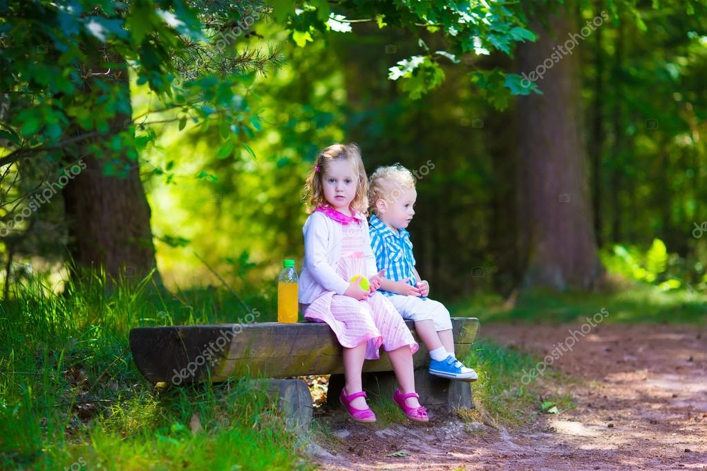 Kids on a bench in a summer forest