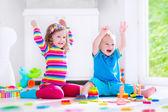 Děti hrají s dřevěnými bloky