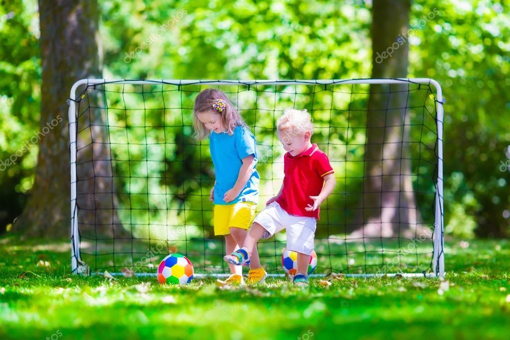 Dos niños felices jugando al fútbol europeo al aire libre en el patio de la  escuela. Los niños juegan fútbol. Deporte activo para el niño preescolar. 101e710efba4d