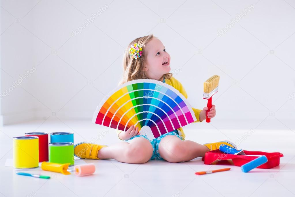 Little girl choosing paint color for wall