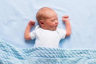 Newborn baby boy under a blue blanket