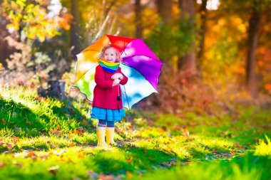 Little girl playing in the rain in autumn