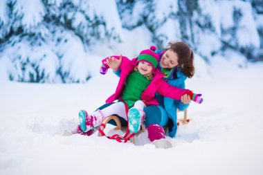Young mother and little girl enjoying sleigh ride. Child sledding. Toddler kid riding sledge. Children play outdoors in snow. Kids sled in snowy park. Outdoor winter fun for family Christmas vacation. stock vector