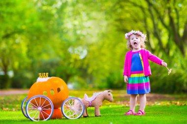 Little girl at pumpkin patch at Halloween
