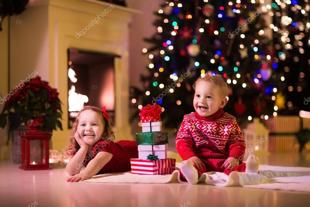 Kids opening Christmas presents at fireplace — Stock Photo ...