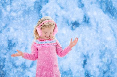 Little girl catching snow flakes