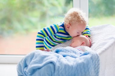 Little boy kissing newborn baby brother