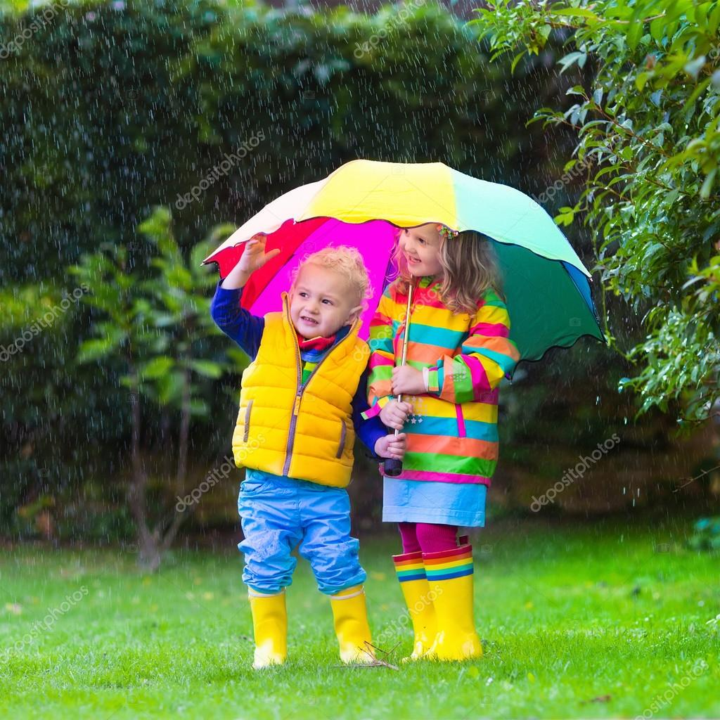 Kids playing in the rain under colorful umbrella