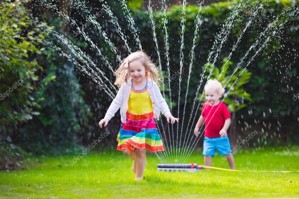 Kids playing with garden sprinkler