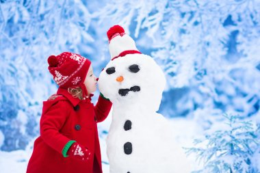 Little girl building snow man in winter