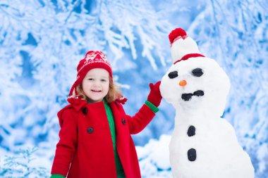 Little girl building a snow man