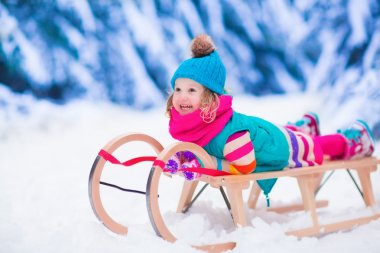 Little girl enjoying a sleigh ride. Child sledding. Toddler kid riding a sledge. Children play outdoors in snow. Kids sled in the Alps mountains in winter. Outdoor fun for family Christmas vacation. stock vector