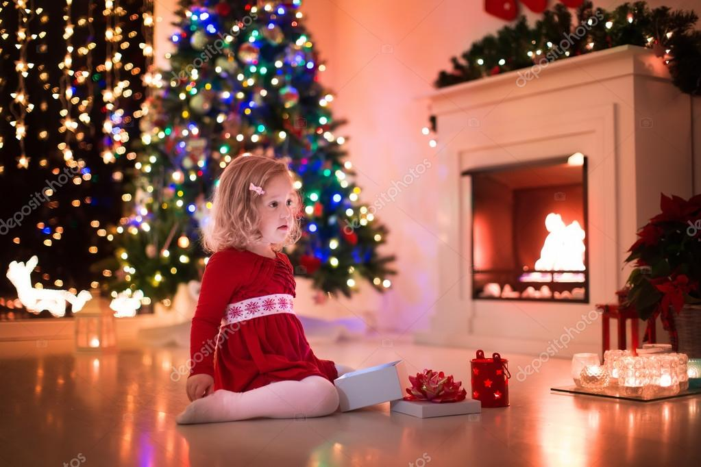 Little girl opening Christmas presents at fire place — Stock Photo ...
