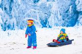 Fotografie Kinder Spaß auf einem Schlitten fahren im winter