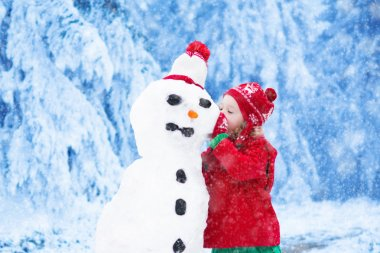 Funny little toddler girl in a red knitted Nordic hat and warm coat playing with a snow man. Kids play outdoors in winter. Children having fun at Christmas time. Child building snowman at Xmas.