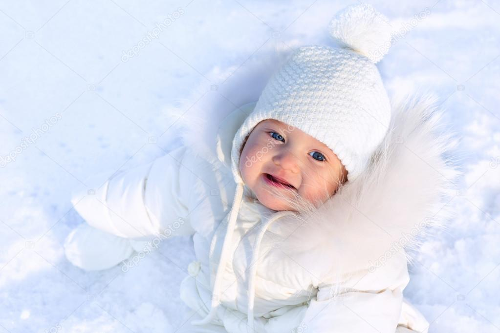 4bd68b7ea Cute little baby in a white jacket and white hat sitting in fres ...