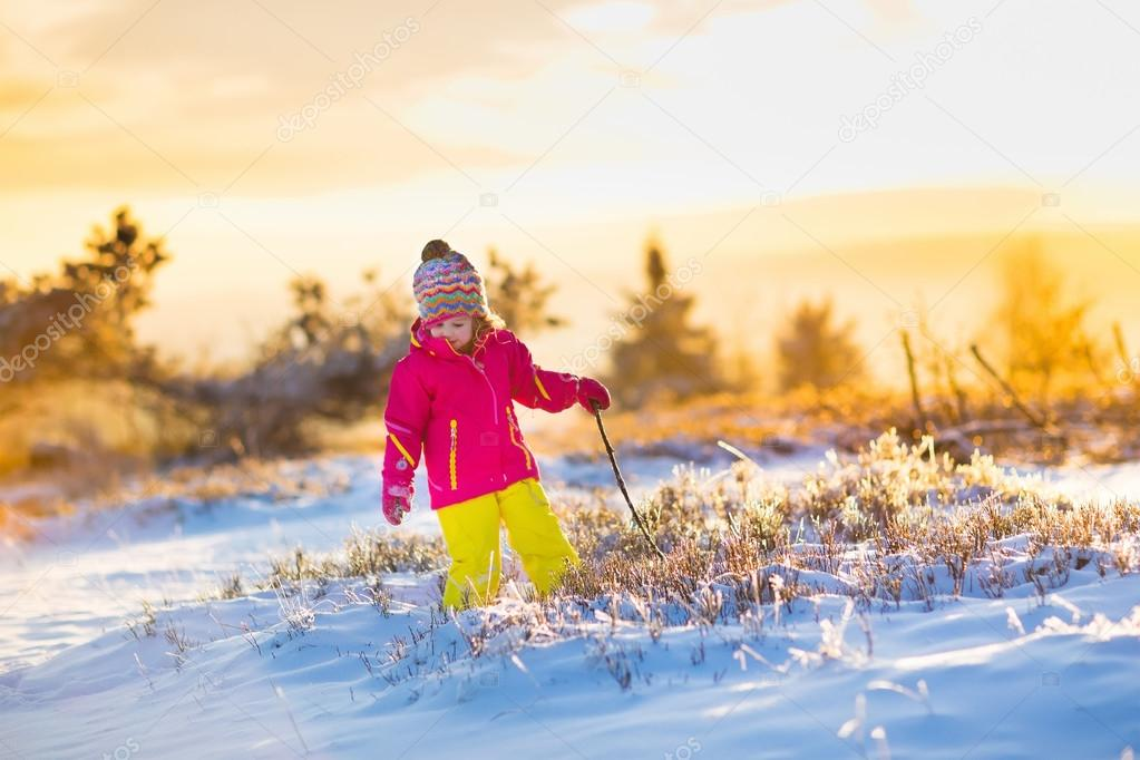 Child having fun in snowy winter park
