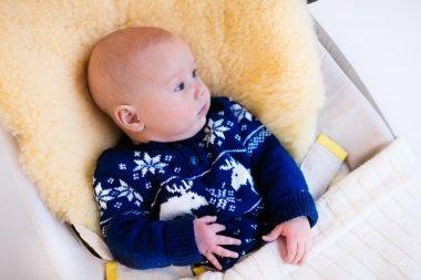 Little baby in nordic sweater on sheepskin muff