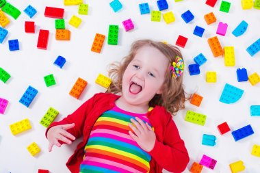 Little girl playing with colorful blocks