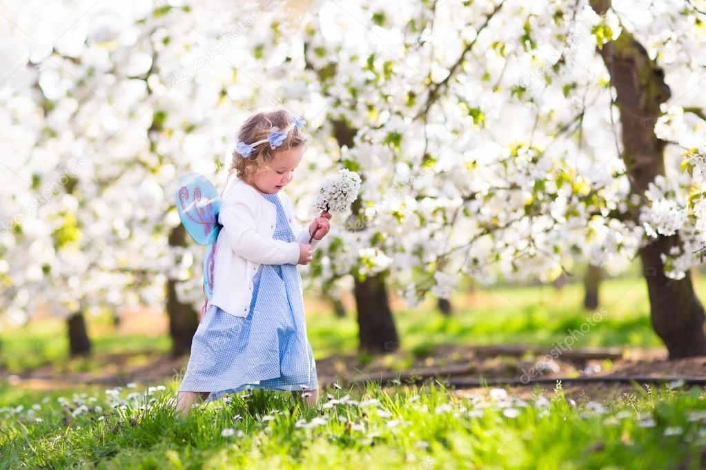 Little girl in apple tree garden