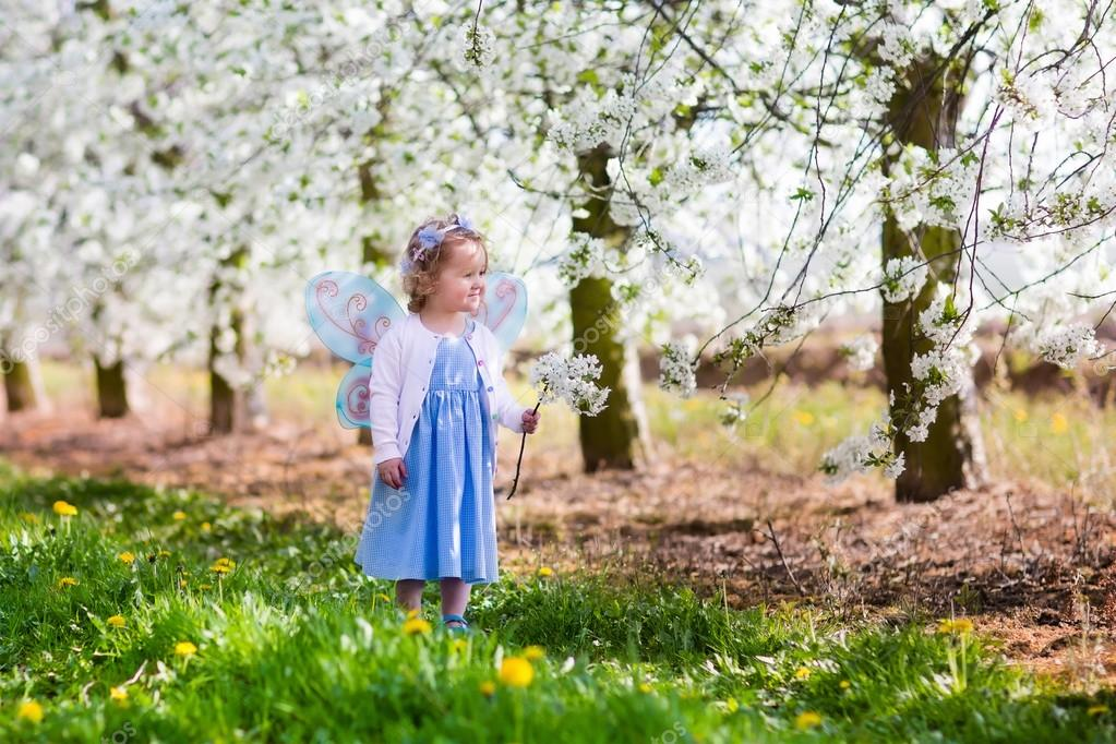 Little girl in apple tree garden