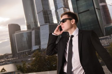 Businessman talking on the phone background of skyscrapers.