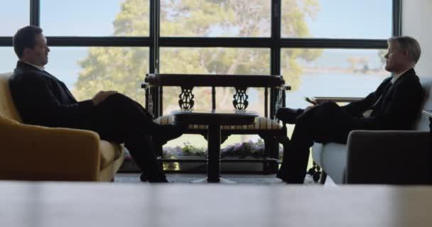 Dva dospělí podnikatelé, kteří mají schůzku v hotelové hale, vedou vážnou konverzaci. Real time, long shot.