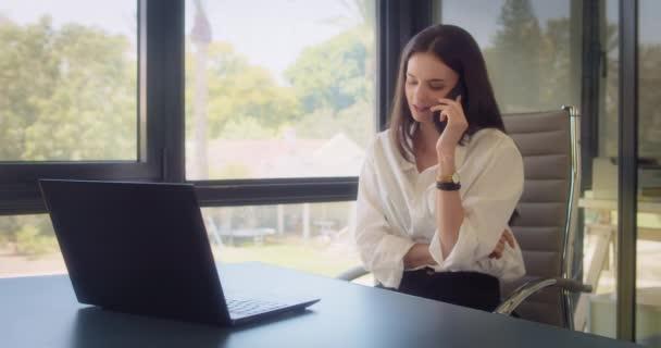 Eine Geschäftsfrau telefoniert, lächelt, während sie im Büro arbeitet. Tracking Medium Shot, Zeitlupe.