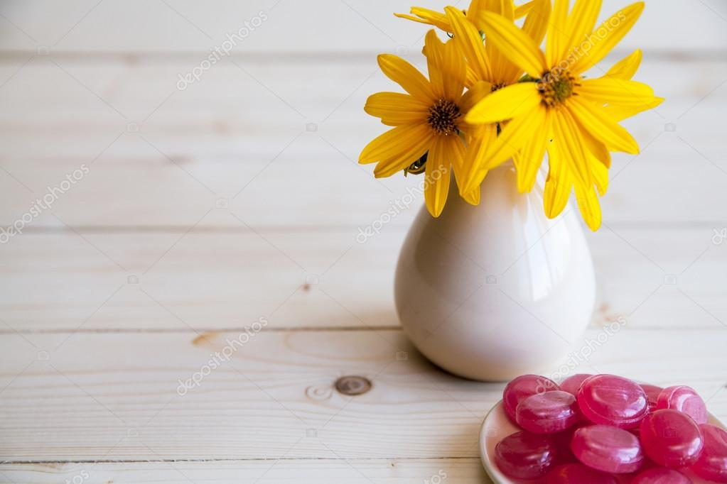 yellow flowers in a vintage vase with red candies on a wooden ba