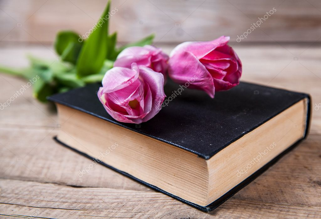 Flowers. pink tulips on a pile of old books