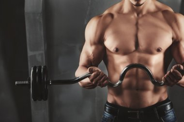 Close up of young muscular man lifting weights over dark background