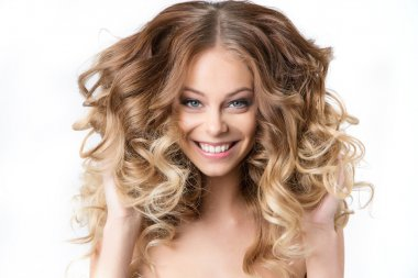 Portrait of beautiful young smiling girl with luxuriant hair curling. Health and Beauty.