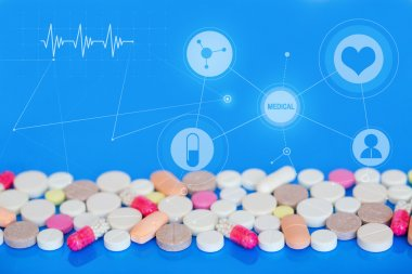 Colored pills on a blue background. Medical concept.