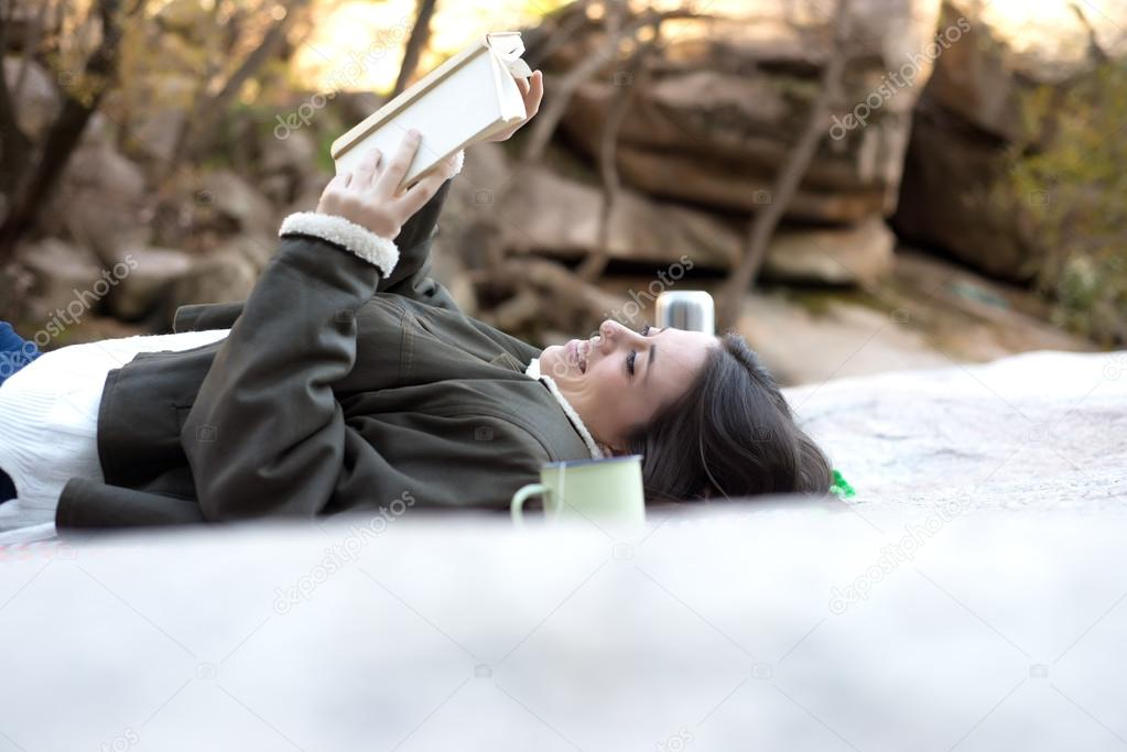 Pretty Woman reading a Book on a Rock