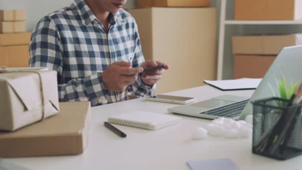Muži pořizují fotografie zboží a posílají je zákazníkům při objednávce online. Muži nahrávají fotografie mobilních telefonů na webovou stránku k prodeji online. Online Trading Trend Ideas.