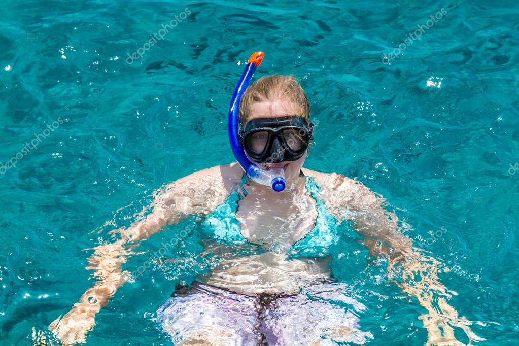 Girl with diving mask swimming in sea