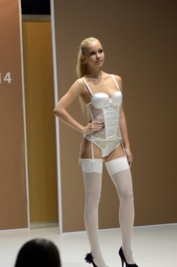 5th International Exhibition of underwear, beachwear, home wear and hosiery Lingrie Expo Moscow Aututumn September Young blonde woman in lingerie and white stockings Desire