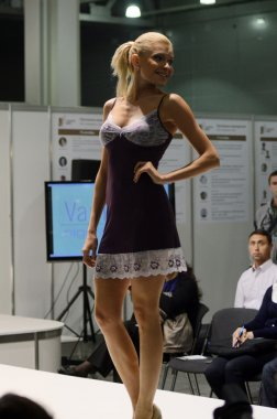 5th International Exhibition of underwear, beachwear, home wear and hosiery Lingrie Expo Moscow Aututumn September Young blonde woman in a purple negligee
