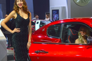 Young womens from Team Maserati. Gran Turismo. Red car Look Moscow International Automobile Salon Premium
