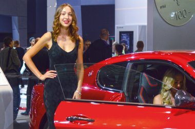 A young woman from the Maserati team. In the long black dress near car. Gran Turismo. Red Car. Moscow International Automobile Salon Look