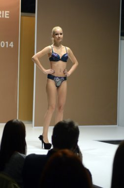 5th International Exhibition of underwear, beachwear, home wear and hosiery Lingrie Expo Young beautiful blonde girl in a blue-black lingerie with flowers
