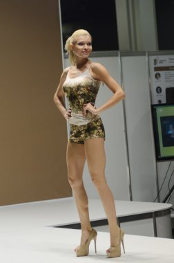 Moscow Traffic 5th International Exhibition of underwear, beachwear, home wear and hosiery Lingrie Expo Young blonde woman in a colorful blouse and shorts with high heels
